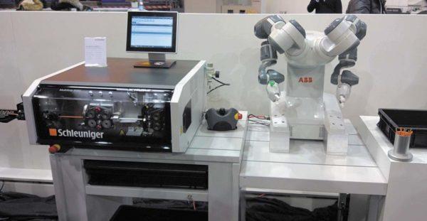 Работа линии мерной резки и зачистки производства компании Schleuniger AG с коботом на основе двух манипуляторов