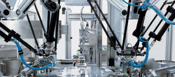 Сборочный автомат электромагнитных реле. Два Трипода используются для установки контактов