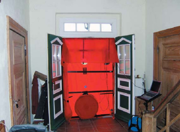 При испытании на воздухонепроницаемость в дверном проеме устанавливается вентилятор, который высасывает воздух из здания, из-за чего воздух снаружи устремляется в здание через все доступные трещины и щели