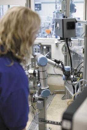 Сотрудник без защитного ограждения контролирует работу робота, анализ содержимого банки и его розлив по фильтрам